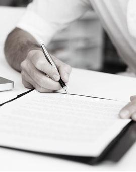 osoba podpisująca długopisem dokumenty
