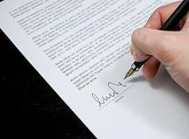 Dłoń trzymająca pióro na kartce z umową